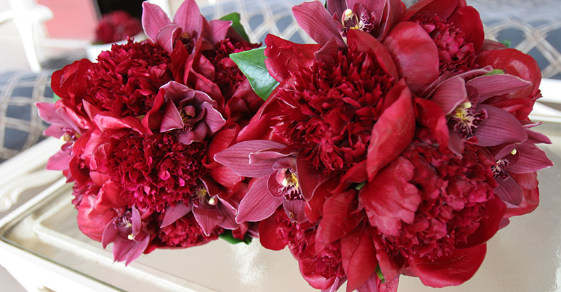 red peonies in brides bouquet