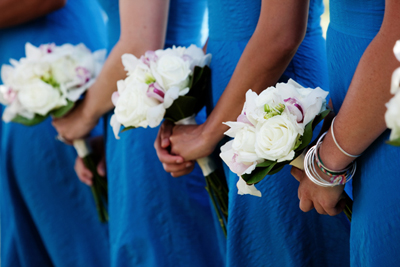 bridemaids with blue dresses and white flowers
