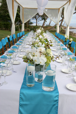 long dinner table set with white orchids